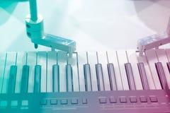 De mekaniska händerna av en robot som spelar pianot arkivfoto
