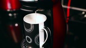 De melk giet in de kop van Koffiemachine stock videobeelden