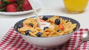 De Melk van het ochtendontbijt het gieten in kom met cornflakes en bessen stock video