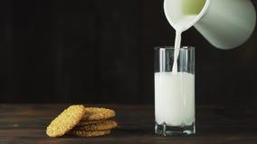 De melk wordt in een traag tempo gegoten in een glas, ideaal voor een dieet voor een gezonde voeding en kan als geneeskunde worde stock video