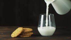 De melk wordt in een traag tempo gegoten in een glas, ideaal voor een dieet voor een gezonde voeding en kan als geneeskunde worde stock footage