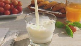 De melk wordt gegoten in een glas langzame motie stock videobeelden