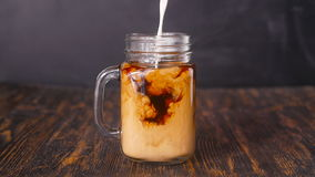 De melk wordt gegoten in koffie stock video