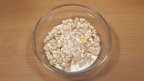 De melk wordt gegoten in plaat met droog ontbijt, langzame motie stock videobeelden