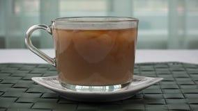 De melk wordt toegevoegd aan een glaskop met thee stock footage