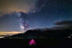 De melkachtige sterren van de maniermelkweg over de Alpen, het kamperen verlichte tent, van Mars en van Jupiter planeet, snowcapp stock afbeeldingen