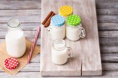 De melkkruiken met kleurrijke kappen op een knipsel schepen, kaneel en het drinken stro in Stock Afbeeldingen