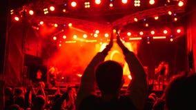 De menigte van mensen het slaan overhandigt hoofden op rotsfestival door heldere schijnwerpers wordt verlicht die