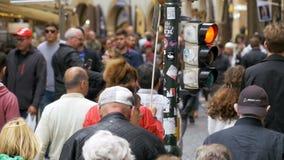 De menigte van mensen kruist de weg dichtbij een verkeerslicht op een voetgangersoversteekplaats Langzame Motie stock video