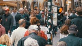 De menigte van mensen kruist de weg dichtbij een verkeerslicht op een voetgangersoversteekplaats Langzame Motie stock videobeelden