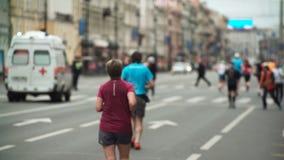 De menigte van mensen stelt marathon op weg in stadscentrum in werking De mannen en de vrouwen in sportkleding nemen aan ras op s stock footage