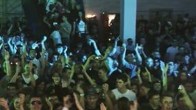 De menigte van mensenklap, heft handen op Het spinnen van DJ bij draaischijf op partij in nachtclub apparatuur stock videobeelden