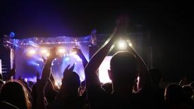 De menigteklap van handen hief overheadkosten op rotsfestival in op openlucht, heffen de mensen wapens op en juichen musici in he stock videobeelden