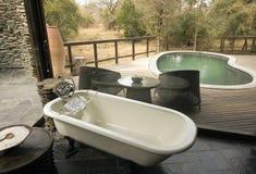 De mening die van de badkamers een pool en een houten dek overziet Royalty-vrije Stock Foto's
