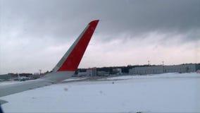 De mening door de rode vleugel die van het vliegtuigvenster zich door luchthavenbaan bewegen, vliegtuig komt aan stock footage