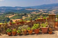 De mening over de Heuvels van Toscanië, Potten van Bloemen is gevoerd langs Bal Stock Foto's