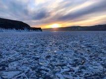 De mening van de avond Barsten op de oppervlakte van het blauwe ijs Bevroren meer Baikal in de winterbergen Het sneeuwt De heuvel stock afbeeldingen
