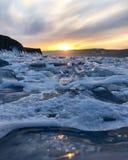 De mening van de avond Barsten op de oppervlakte van het blauwe ijs Bevroren meer Baikal in de winterbergen Het sneeuwt De heuvel royalty-vrije stock afbeeldingen