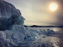 De mening van de avond Barsten op de oppervlakte van het blauwe ijs Bevroren meer Baikal in de winterbergen Het sneeuwt De heuvel royalty-vrije stock foto's