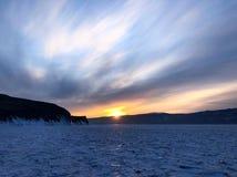 De mening van de avond Barsten op de oppervlakte van het blauwe ijs Bevroren meer Baikal in de winterbergen Het sneeuwt De heuvel stock afbeelding