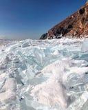 De mening van de avond Barsten op de oppervlakte van het blauwe ijs Bevroren meer Baikal in de winterbergen Het sneeuwt De heuvel stock foto