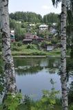 De mening van de banken van de rivier aan de berg in kleine dorpshuizen door Russische witte berk Stock Fotografie