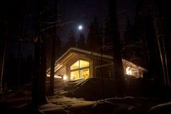 De mening van de nacht van houten plattelandshuisje. Stock Afbeelding