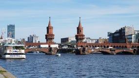 De mening van de rivierfuif van Schillingbrà ¼ cke overbrugt met een gele trein die de Oberbaum-Brug op de achtergrond, Berlijn d royalty-vrije stock foto