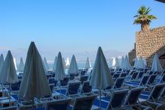 De mening van de stoelen en gesloten sunshades tegen de heldere Zonnige hemel, het azuurblauwe overzees en de bergketen Vroege oc Royalty-vrije Stock Fotografie