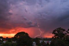 De mening van de zonsondergangonweersbui van park over de stad met bouten en Royalty-vrije Stock Afbeelding