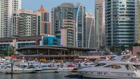 De mening van Doubai Marina Towers dacht in water van kanaal in de dag van Doubai na aan nacht timelapse stock video