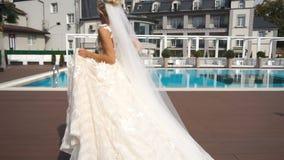De mening van gemiddelde lengte van de schitterende blondebruid die en in de mooie huwelijkskleding dichtbij de pool dansen spinn stock videobeelden