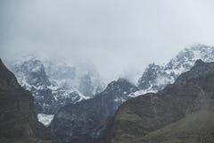 De mening van het aardlandschap van wolken en de mist behandelden de sneeuw afgedekte berg van Ultar Sar, Pakistan royalty-vrije stock afbeelding