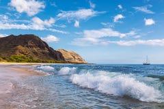De mening van het Makuastrand van de golf met mooie bergen en een zeilboot op de achtergrond, Hawaï stock fotografie