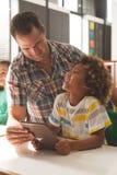 De mening van het oppervlakteniveau van een leraar die met een schooljongen interactie aangaan over een digitale tablet royalty-vrije stock afbeeldingen