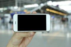 De mening van het smartphonelandschap van de handholding met luchthavenachtergrond Stock Foto's