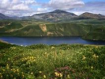 De mening van het Sopochnoyemeer met bloemenweide op zonnige dag Iturup, Kuril Eilanden, Rusland Stock Afbeeldingen