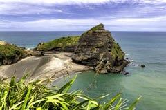 De mening van het Taitomoeiland bij Piha-Strand, Auckland, Nieuw Zeeland Royalty-vrije Stock Afbeelding