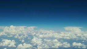 De mening van het vliegtuigvenster aan de blauwe hemel en witte wolken op een zonnige dag, veel witte wolken drijft boven stock videobeelden