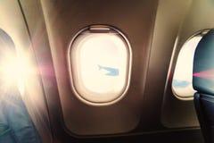 De mening van het vliegtuigvenster binnen een vliegtuig Venstervliegtuig bij zonsopgang Stock Fotografie