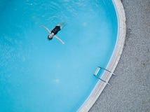 De mening van het vogelsoog van een openluchtpool en een lang meisje van het haar zwart zwempak zwemt in het water royalty-vrije stock afbeeldingen