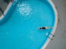 De mening van het vogelsoog, jong meisje in zwart zwempak, springt in een zwembad Royalty-vrije Stock Foto
