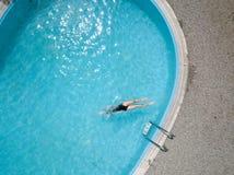 De mening van het vogelsoog, jong meisje in zwart zwempak, springt in een zwembad Royalty-vrije Stock Afbeelding