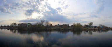 De mening van het zonsondergangmeer met dorpsachtergrond Stock Afbeelding