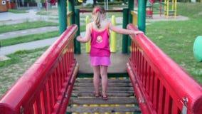 De mening van meisje gaat op kabelbrug in playset bij speelplaats stock video