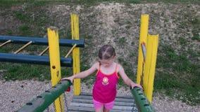 De mening van meisje gaat op kabelbrug in playset bij speelplaats stock videobeelden