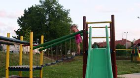 De mening van meisje gaat op kabelbrug in playset bij speelplaats Meisje op de dia bij speelplaats stock footage