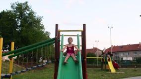 De mening van meisje gaat op kabelbrug in playset bij speelplaats Meisje op de dia bij speelplaats Lage DOF stock video