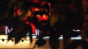 De mening van de Moulinrouge door boombladeren bij nacht, Parijs stock footage