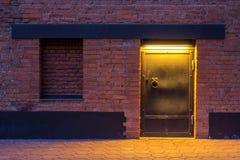 De mening van de nacht De ingang aan het pakhuis Een staaldeur in een bakstenen muur royalty-vrije stock fotografie